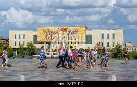 Touristen marschieren auf dem Skanderbeg-Platz vor dem nationalen Geschichtsmuseum. Das Mosaik über dem Museum nannte Die Albaner, die die Geschichte der natio erzählen - Stockfoto