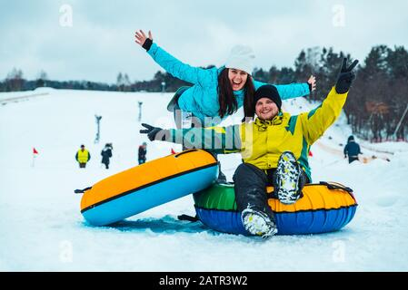 Paar Spaß mit Snow tube nach unten schieben - Stockfoto