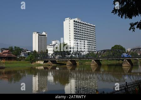 Iron Bridge (Sapaan Lek) überspannt den Fluss Mae Ping mit dem Pornping Tower und den Diamond Riverside Hotels im Hintergrund, Chiang Mai, Thailand - Stockfoto