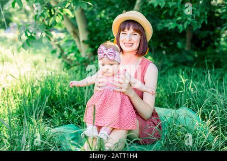 Eine glückliche Familie, die an einem sonnigen Frühlingstag im grünen Garten ein Picknick macht: Eine schöne lächelnde Mutter, die auf grünem Gras sitzt und ihr wenig lacht - Stockfoto