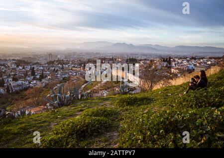 Granada, Spanien - 17. Januar 2020: EIN Paar blickt auf Granada bei Sonnenuntergang an den Albaicin-Stadtmauern am San Miguel Alto Aussichtspunkt. - Stockfoto