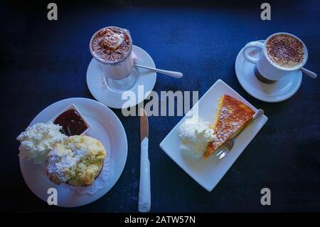 Draufsicht auf zwei Tassen Kaffee mit Scone mit Schlagsahne und Kuchen - Stockfoto