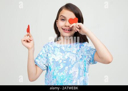 Schönes kaukasisches junges Mädchen, das zwei Karten in Form eines Herzens für den Valentinstag auf einem hellen Hintergrund hält - Stockfoto