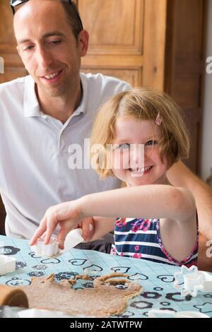 Mädchen im Alter von 5 / 5 Jahren und ihr Onkel, die beim Backen von Keksrezept aus Zutaten/Keksen eine Gebäckschneide verwenden; Hauskochbäcke mit Kindern/Kindern. (112) - Stockfoto
