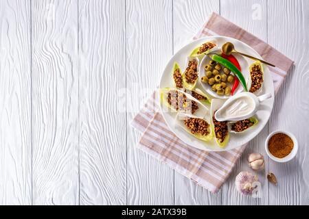 Würziges gemahlenes Rindfleisch und gehackte grüne Oliven Endive-Boote werden auf einem weißen Teller mit Sauerrahm, Oliven, Chilipern, horizontaler Ansicht von oben, fl serviert