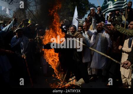 Februar 2020: Peschawar, Pakistan. Februar 2020. Die Pakistaner inszenieren einen Protest zum Kaschmir-Solidaritätstag in der pakistanischen Stadt Peshawar. Die Teilnehmer winkten Banner und skandierten Slogans zur Unterstützung Indiens verwalteten Kaschmir und Kasmiris Kampf um ihr Recht auf Selbstbestimmung. Die indianische Flagge und ein Effigie des indischen Präsidenten Narendra Modi wurden während des Protestes am Mittwoch in Aufleuchten gebracht. Kinder schlossen sich auch der Kundgebung an, die Pakistan und die Flagge Azad Jammu und Kaschmirs in Solidarität mit den Kaschmiris schwenkte. Der indische Staat Jammu und Kaschmir war stark eingeschränkt - Stockfoto