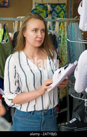 Hübsche Frau, die sich im Urlaub für Flip-Flops im Geschäft entscheidet. - Stockfoto