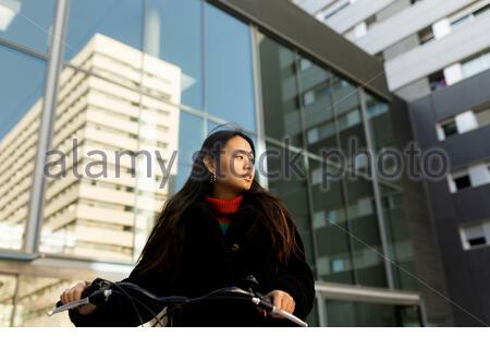 Junge Frau trägt schwarze Jacke zu Fuß mit dem Fahrrad