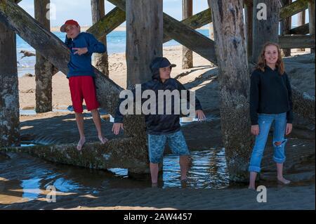 Kinder posieren spielerisch unter einem Pier im Siletz Bay Park in Lincon City an der Oregon Coast - Stockfoto