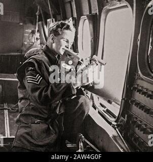 Ein Mobilfunkanbieter, der eine andere Rolle als Kameramann übernimmt, da er eine F24-Kamera durch die offene Tür einer Lockheed Hudson verwendet. - Stockfoto