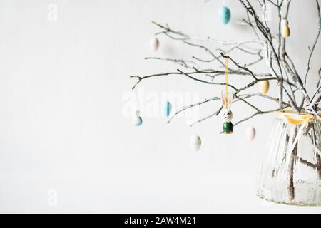 Stillleben mit Baumzweigen, die mit Ostereiern, Federn und Hasen in einer Glasvase verziert sind - Stockfoto