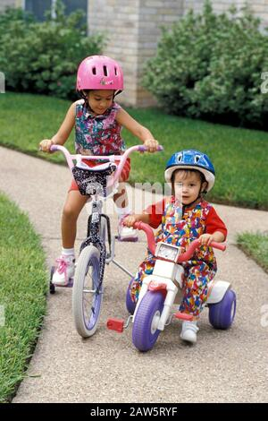 Hispanische Schwestern im Alter von 5 und 2 Jahren, die mit dem Fahrrad und dem Dreirad auf dem Bürgersteig vor ihrem Haus in Austin, Texas USA fahren. Ältere Schwester fährt ein Fahrrad mit Trainingsrädern, während jüngere Schwester auf einem kleinen Kunststoffdreirad steht - Stockfoto