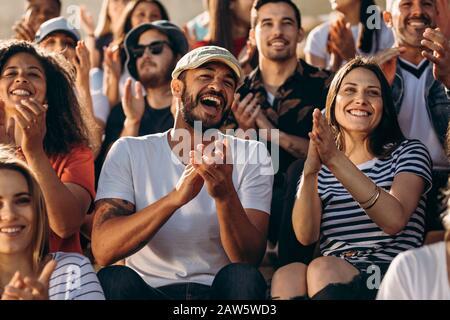 Gruppe von Menschen, die eine Sportveranstaltung und Jubel beobachten. Aufgeregte Menge von Sportfans, die im Stadion sitzen.