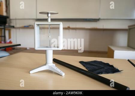 Herkömmliches Elektroskop mit Stab und Tuch, das zur Demonstration in einem Klassenzimmer verwendet wird. Physik-Experiment. - Stockfoto