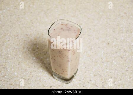 Klares Glas Vanille-Smoothie auf dem passenden Marmorkonsenoberteil - Stockfoto