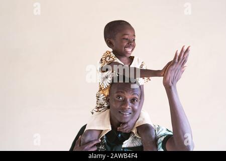 Echte afrikanische Familie von Papa und Sohn hoch fünf vor der Kamera als lächelndes Glückssymbol - Stockfoto