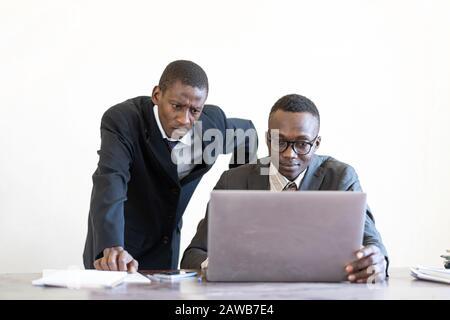 Afrikanische zwei Menschen denken in ihrem Büro vor dem Laptop - Stockfoto