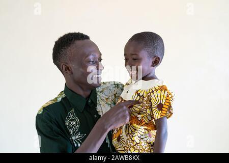Afrikanischer Papa kitzelt sein Kind an und macht sich glücklich lächelnd lustig und lacht zusammen als Symbol für Vielfalt - Stockfoto