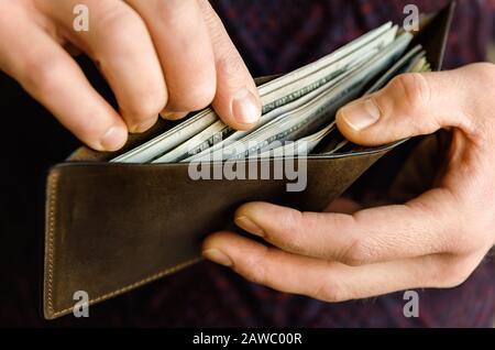 Geldbörse aus braunem Leder mit Dollar in den Händen. Nahaufnahme. - Stockfoto