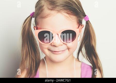 Kleines glückliches Mädchen in Sonnenbrille und mit Kopfhörern lachend - Studio erschossen - Stockfoto