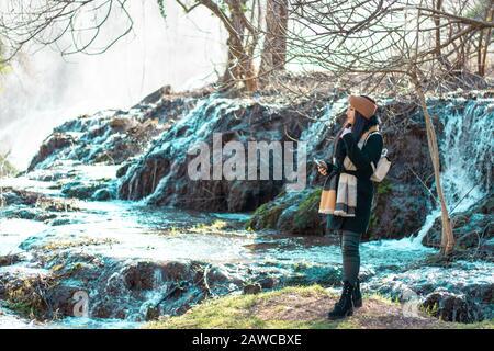 Mädchen Reisenden, die auf einem moosigen Flecken Gras stehen, ein kalter Fluss, der im Hintergrund fließt. Kravice-Wasserfall in bosnien an einem kalten Wintertag - Stockfoto