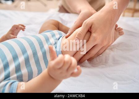 Babypflege. Junge Mutter massiert bei Kindern die Beine des kleinen Sohnes, der auf dem Bett in der Nähe liegt