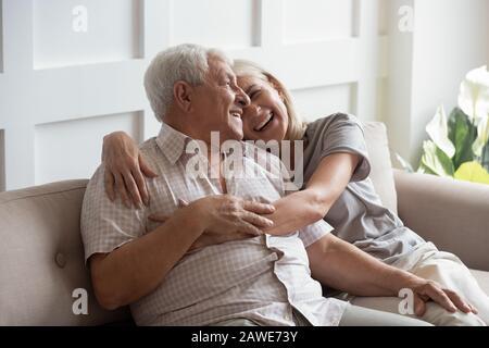 Glücklicher älterer Mann und Frau entspannen sich auf der Couch - Stockfoto