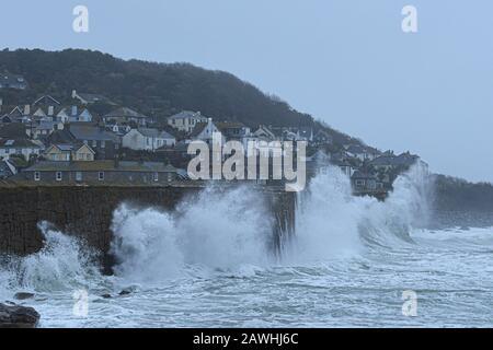 Mousehole, Cornwall, Großbritannien, 9. Februar 2020. Wetter in Großbritannien. Wellen fahren mehrere Stunden nach Flut heute Morgen über dem hohen Hafen walla bei Mousehole an den Strand, als Sturm Ciara Cornwall trifft. Credit Simon Maycock / Alamy Live News. - Stockfoto