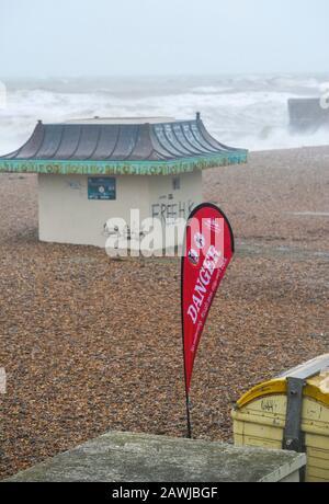 Brighton UK 9. Februar 2020 - EIN Gefahrenschild am Strand von Brighton, während Storm Ciara Großbritannien mit Bernsteinwarnungen im ganzen Land trifft, da hohe Winde zu Schäden und möglichen Lebensgefahr führen sollen: Kredit Simon Dack / Alamy Live News - Stockfoto
