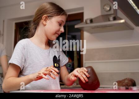 Mädchen hilft, einen Teig für ein traditionelles Weihnachtsgericht zu machen - Stockfoto