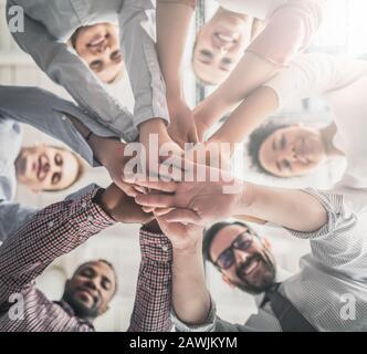 Nahaufnahme der jungen Geschäftsleute, die ihre Hände zusammenlegen. Handstapel. Einigkeit und Teamarbeit. - Stockfoto