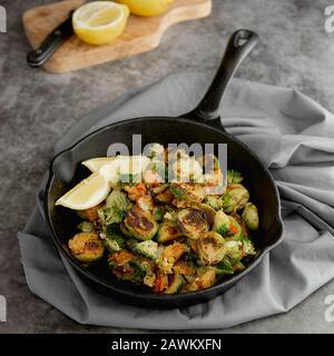Geröstete brüsseler Sprossen in eiserner Pfanne mit Zitronenscheiben. Dunkler Hintergrund. Quadratisches Bild. Gesundes Lebensmittelkonzept. - Stockfoto