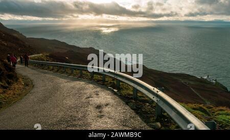 Menschen, die bei dramatischen Witterungsbedingungen im Winter zum Mull of Kintyre Leuchtturm mit Blick auf Nordirland und die Rathlin-Insel spazieren gehen, Scot - Stockfoto