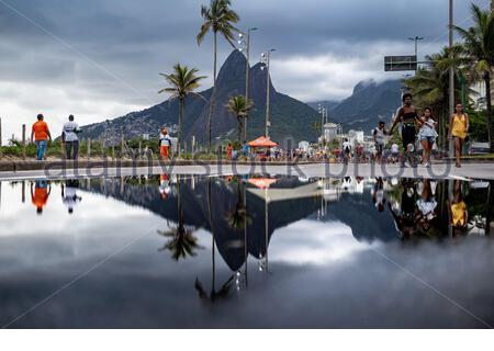 Große Pfütze nach Regen, der zwei Brüder am Berg (Dois Irmaos) auf dem Bürgersteig in der Nähe des Strandes von Ipanema/Leblon in Rio de Janeiro, Brasilien reflektiert. Leica M10 - Stockfoto