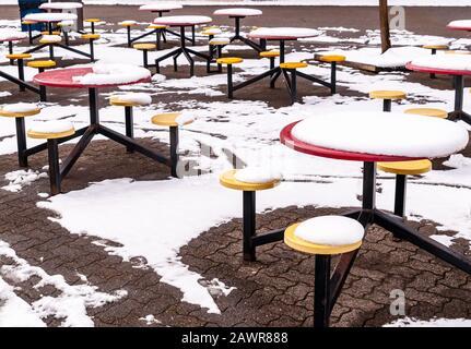 Picknicktische aus Metall, die im Winter in Pittsburg, Pennsylvania, USA im schmelzenden Schnee liegen - Stockfoto