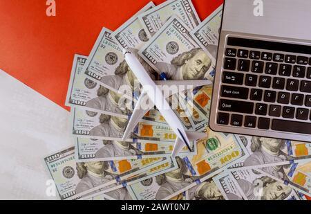 Bargeld in amerikanischen Dollarscheinen mit Plastikflugzeugmodell und Laptop-Computertastatur - Stockfoto