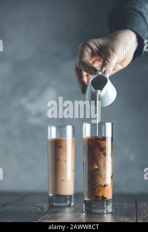 Frauen Hand gießt hausgemachte saure Sahne aus kleinem Glas auf Glas mit kältem Kaffee und Eis. Kaltes Sommergetränk auf dunklem Holztisch und grauem Bac - Stockfoto