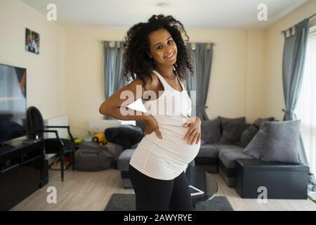 Portrait fröhliche junge schwangere Frau im Wohnzimmer - Stockfoto