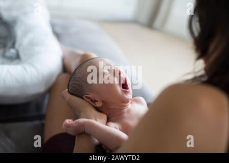 Mutter hält weinenden Neugeborenen Sohn - Stockfoto