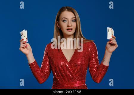 Elegantes blondes Mädchen mit Make-up, tätowierte Hand, in rotem Paillettenkleid zeigt vier Asse, wundert aussehend, posiert vor blauem Hintergrund. Glücksspiel - Stockfoto