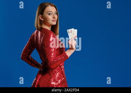 Nettes blondes Mädchen mit Make-up, in rotem Paillettenkleid zeigt zwei Asse, seitlich vor blauem Hintergrund posiert. Glücksspiel Unterhaltung, Poker, Casino - Stockfoto