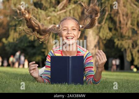 Ihre Frisur fliegen. Glückliches Kind mit fliegenden Frisur auf grünem Gras. Kleine süße Mädchen lächeln mit langen Schwänzen Frisur. Mode Aussehen der einfache Frisur. Buchen Sie wissen. Friseursalons. Friseursalon. - Stockfoto
