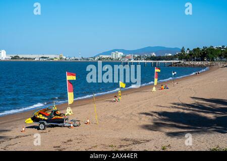 Surfen Sie am Strand von The Strand, Townsville, Queensland, Australien, mit Lebensrettenden Flaggen - Stockfoto