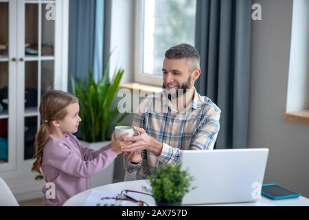 Kleine Tochter, die ihrem lächelnden Vater eine Tasse aushält. - Stockfoto
