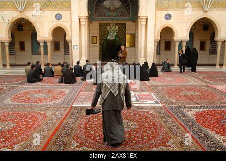 Iranische Pilger sitzen im Hof der Sayyaden-Ruqayya-Moschee, Damaskus, Syrien. - Stockfoto