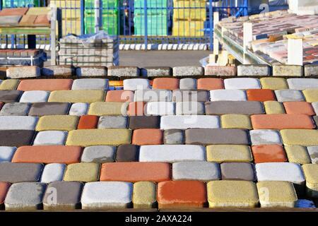 Ziegelsteine und Pflastersteine an der Baustelle. Lagerpflasterstplatten für die Verlegung der Straße. Bau von Bürgersteigen. - Stockfoto