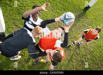 Dreizehn Jahre alte Jungen, die an einer weiterführenden Schule in Großbritannien Rugby spielen - Stockfoto
