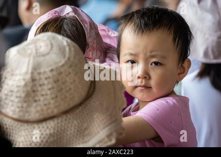Zhangjiajie, China - August 2019: Kleines chinesisches Mädchen, das von ihrer Mutter in einer Warteschlange am Eingang von Wullingyuan zum Zhangjiajie National gehalten wird - Stockfoto