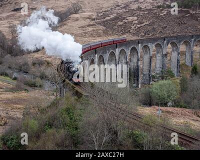 Die Jacobite Steam Train Crossing Glenfinnan Viaduct auf der Strecke von Fort William nach Mallaig in Schottland. GROSSBRITANNIEN. Stockfoto
