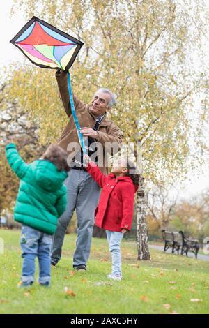 Großvater und Enkel fliegen im Herbstpark einen Drachen - Stockfoto